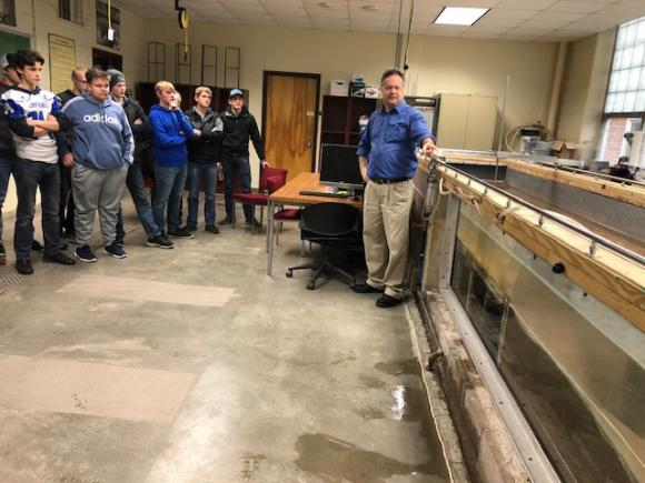 Dr. Brian Barkdoll (Civil & Environmental Engineering) shows students a stream model used to measure the erosion impacts of high stream flows on bridge piers.